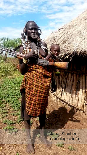 Mursi Woman with a Lip Plate, Gun and Child.