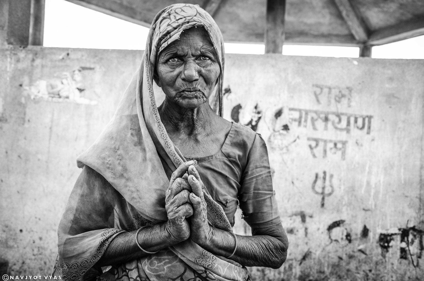 """Fotografii s názvem Ve jménu Boha pořídil NaFotografie s názvem Ve jménu Boha pořídil Navjyot Vyas po cestě domů z práce. Žebrající žena prosící o almužnu """"ve jménu Boha"""" stála shodou náhod před zdí s Božími nápisy - Navjyot rychle zabrzdil své kolo a zachytil tento silný moment.vjyot Vyas po cestě domů z práce. Žebrající žena prosící o almužnu """"ve jménu Boha"""" stála shodou náhod před zdí s Božími nápisy - Navjot tedy zaparkoval své kolo a zachytil tento silný moment. Foto: Navjyot Vyas"""